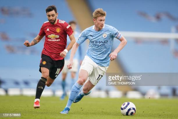 Manchester City's Belgian midfielder Kevin De Bruyne runs with the ball chased by Manchester United's Portuguese midfielder Bruno Fernandes during...