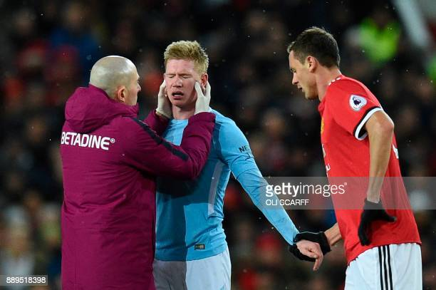 Manchester City's Belgian midfielder Kevin De Bruyne shakes hands with Manchester United's Serbian midfielder Nemanja Matic as he recieves attention...