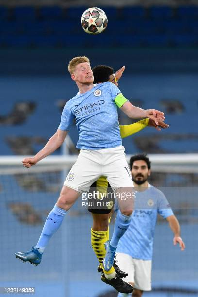 Manchester City's Belgian midfielder Kevin De Bruyne vies with Dortmund's English midfielder Jude Bellingham to header the ball during the UEFA...