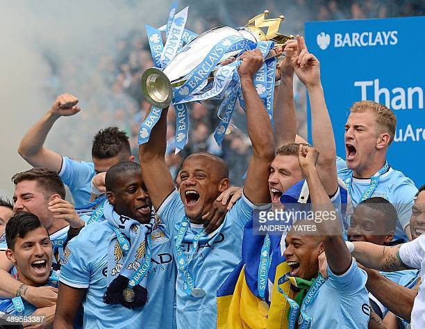 Manchester City's Belgian midfielder Vincent Kompany celebrates with the Premiership trophy after his team won 20 during the English Premier League...