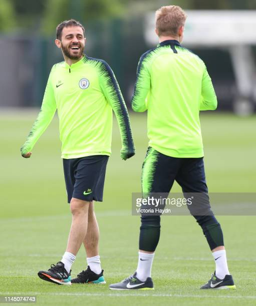Manchester City's Bernardo Silva and Oleksandr Zinchenko react during training at Manchester City Football Academy on April 25 2019 in Manchester...