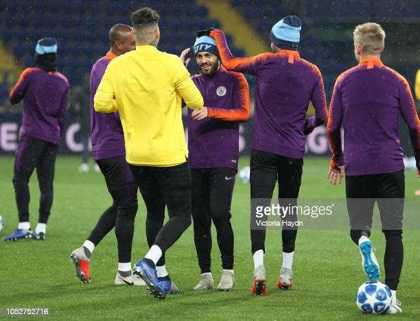 Manchester City's Bernardo Silva Fernandinho Ederson Moraes Riyad Mahrez and Oleksandr Zinchenko share a joke during a training session ahead of...