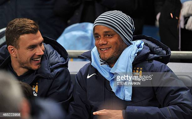 Manchester City's Bosnian striker Edin Dzeko and Manchester City's Belgian defender Vincent Kompany smile on the bench ahead of the English Premier...