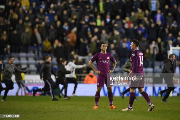 Manchester City's Brazilian defender Danilo and Manchester City's French defender Aymeric Laporte react as supporters invade the pitch after the...