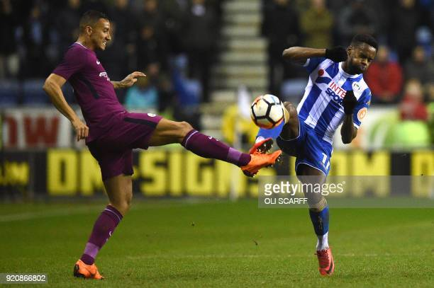 Manchester City's Brazilian defender Danilo is challenged by Wigan Athletic's English striker Gavin Massey during the English FA Cup fifth round...