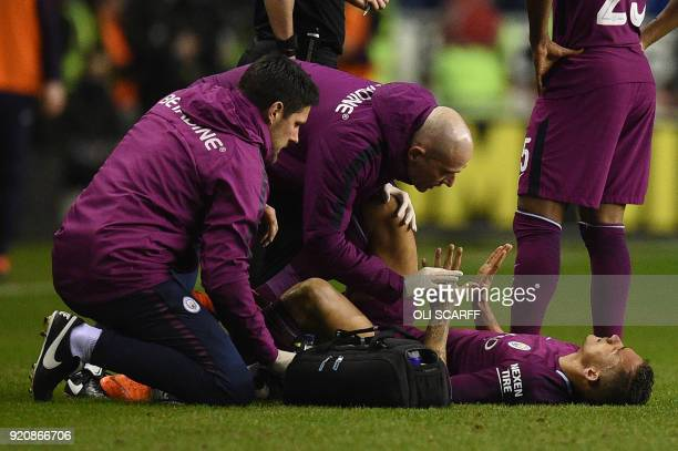 Manchester City's Brazilian defender Danilo receives medical attention during the English FA Cup fifth round football match between Wigan Athletic...