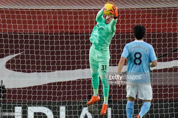 Manchester City's Brazilian goalkeeper Ederson catches the ball during the English Premier League football match between Liverpool and Manchester...