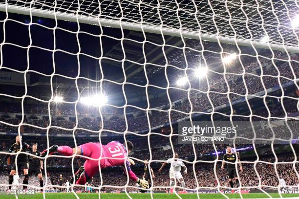 Manchester City's Brazilian goalkeeper Ederson dives for the ball during the UEFA Champions League round of 16 firstleg football match between Real...