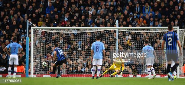 Manchester City's Brazilian goalkeeper Ederson dives the wrong way as Atalanta's Ukrainian midfielder Ruslan Malinovskyi scores the opening goal from...