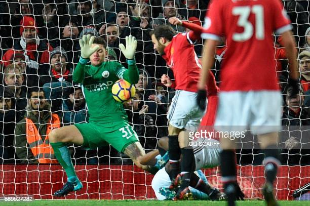 Manchester City's Brazilian goalkeeper Ederson makes the second of a double save from a shot from Manchester United's Spanish midfielder Juan Mata...