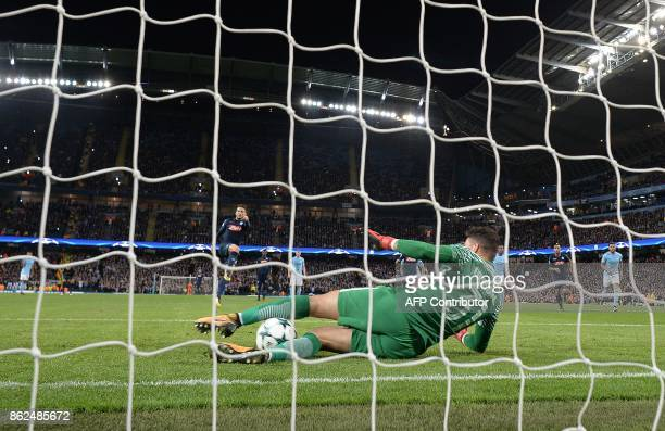 Manchester City's Brazilian goalkeeper Ederson saves a penalty shot from Napoli's Belgian striker Dries Mertens during the UEFA Champions League...