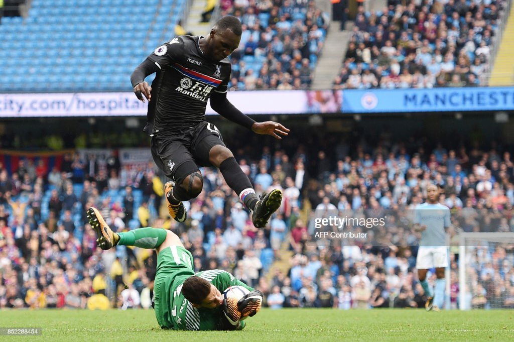 Manchester City's Brazilian goalkeeper Ederson saves the ball from Crystal Palace's Zaire-born Belgian striker Christian Benteke during the English Premier League football match between Manchester City and Crystal Palace at the Etihad Stadium in Manchester, north west England, on September 23, 2017. / AFP PHOTO / Oli SCARFF / RESTRICTED TO EDITORIAL USE. No use with unauthorized audio, video, data, fixture lists, club/league logos or 'live' services. Online in-match use limited to 75 images, no video emulation. No use in betting, games or single club/league/player publications. /