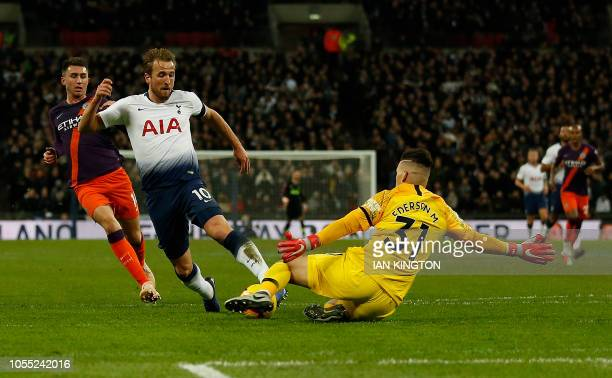 Manchester City's Brazilian goalkeeper Ederson tackles Tottenham Hotspur's English striker Harry Kane during the English Premier League football...