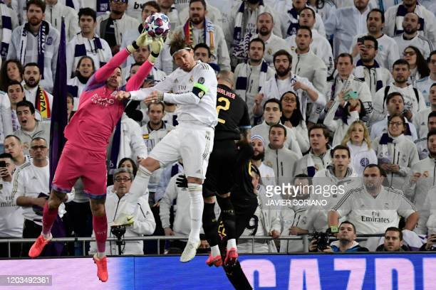 Manchester City's Brazilian goalkeeper Ederson vies with Real Madrid's Spanish defender Sergio Ramos during the UEFA Champions League round of 16...