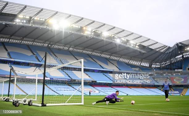 Manchester City's Brazilian goalkeeper Ederson warms up in front of empty stands ahead of the English Premier League football match between...