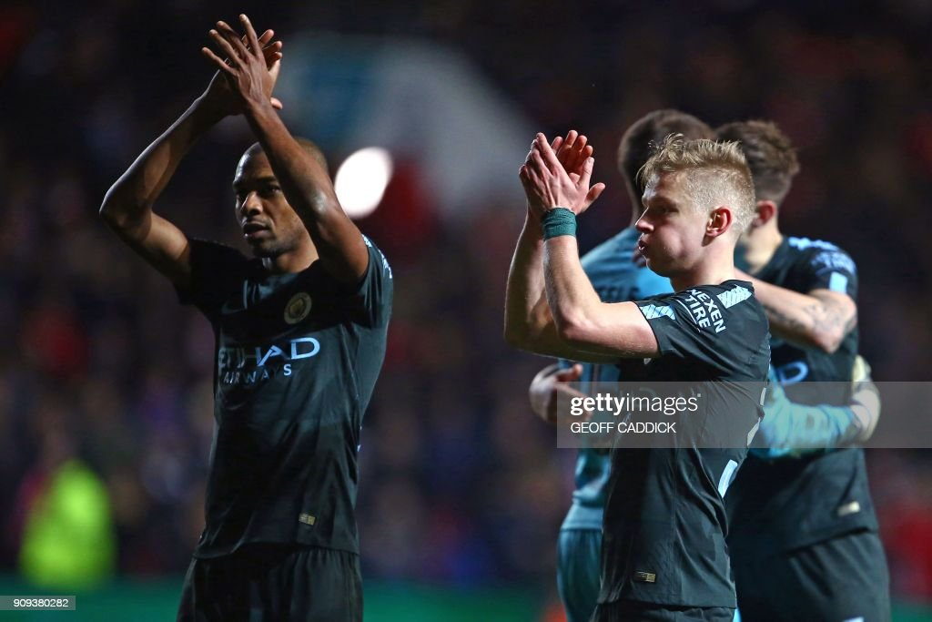 Manchester City's Brazilian midfielder Fernandinho (L) and Manchester City's Ukrainian midfielder Oleksandr Zinchenko applaud supporters on the pitch as they celebrate after the English League Cup semi-final, second leg football match between Bristol City and Manchester City at Ashton Gate Stadium in Bristol, south-west England on January 23, 2018. Manchester City won the game 3-2, (5-3 on aggregate). / AFP PHOTO / Geoff CADDICK / RESTRICTED TO EDITORIAL USE. No use with unauthorized audio, video, data, fixture lists, club/league logos or 'live' services. Online in-match use limited to 75 images, no video emulation. No use in betting, games or single club/league/player publications. /