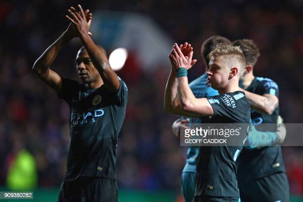 Manchester City's Brazilian midfielder Fernandinho and Manchester City's Ukrainian midfielder Oleksandr Zinchenko applaud supporters on the pitch as...