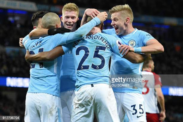 Manchester City's Brazilian midfielder Fernandinho celebrates with teammates after scoring the opening goal during the English Premier League...