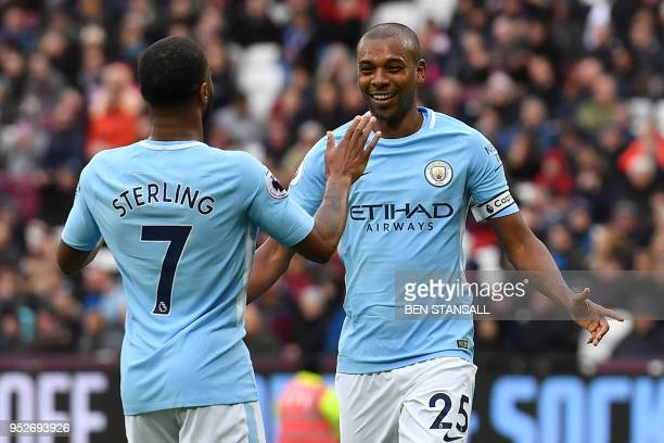 Manchester City's Brazilian midfielder Fernandinho celebrates with Manchester City's English midfielder Raheem Sterling after scoring their fourth...