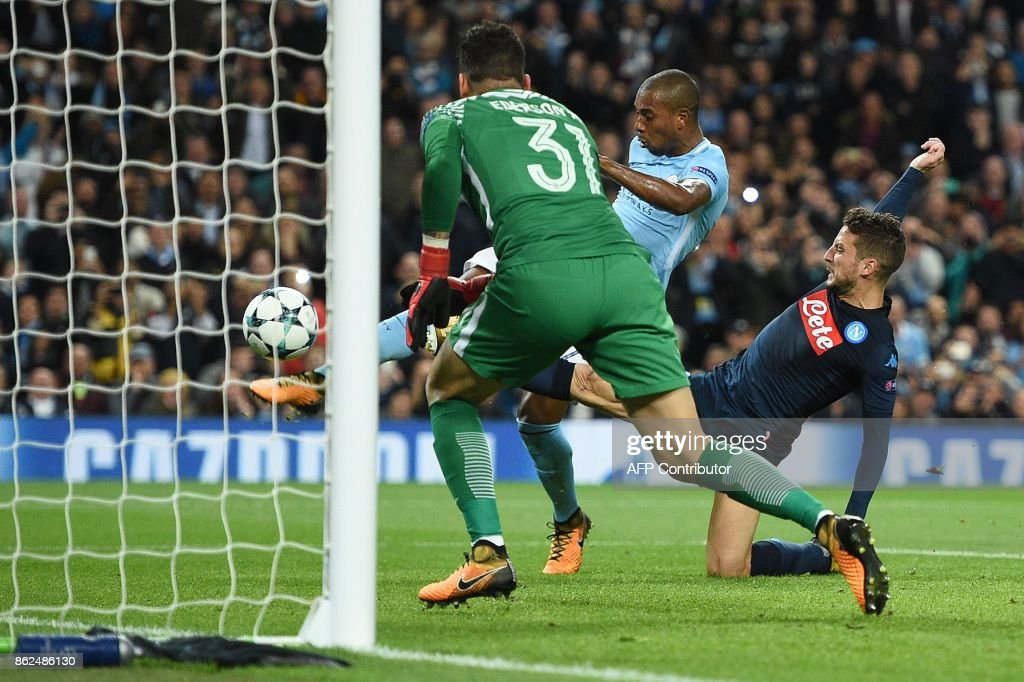 Manchester City's Brazilian midfielder Fernandinho (C) clears the rebounding ball after Manchester City's Brazilian goalkeeper Ederson (L) saved a penalty shot from Napoli's Belgian striker Dries Mertens during the UEFA Champions League Group F football match between Manchester City and Napoli at the Etihad Stadium in Manchester, north west England, on October 17, 2017. / AFP PHOTO / Oli SCARFF