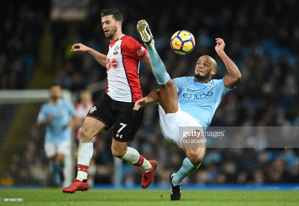 Manchester City's Brazilian midfielder Fernandinho (R) clears the ball from Southampton's Irish striker Shane Long during the English Premier League football match between Manchester City and Southampton at the Etihad Stadium in Manchester, north west England, on November 29, 2017. / AFP PHOTO / Oli SCARFF / RESTRICTED TO EDITORIAL USE. No use with unauthorized audio, video, data, fixture lists, club/league logos or 'live' services. Online in-match use limited to 75 images, no video emulation. No use in betting, games or single club/league/player publications. /