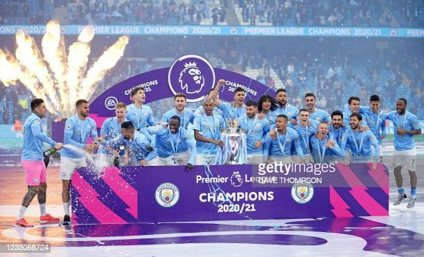 Manchester City's Brazilian midfielder Fernandinho holds the Premier League trophy during the award ceremony after the English Premier League...
