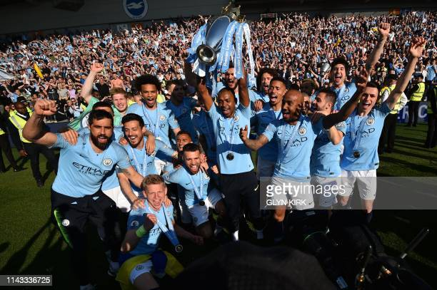 Manchester City's Brazilian midfielder Fernandinho holds up the Premier League trophy as players celebrate on the pitch after their 41 victory in the...