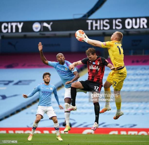 Manchester City's Brazilian midfielder Fernandinho jumps for the ball against Bournemouth's English goalkeeper Aaron Ramsdale and Bournemouth's...