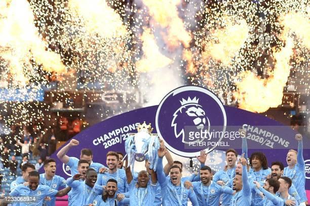 Manchester City's Brazilian midfielder Fernandinho lifts the Premier League trophy during the award ceremony after the English Premier League...