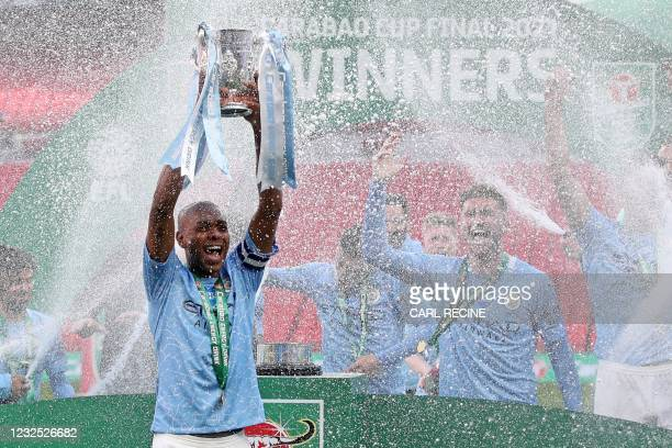 Manchester City's Brazilian midfielder Fernandinho lifts the winners trophy after the English League Cup final football match between Manchester City...