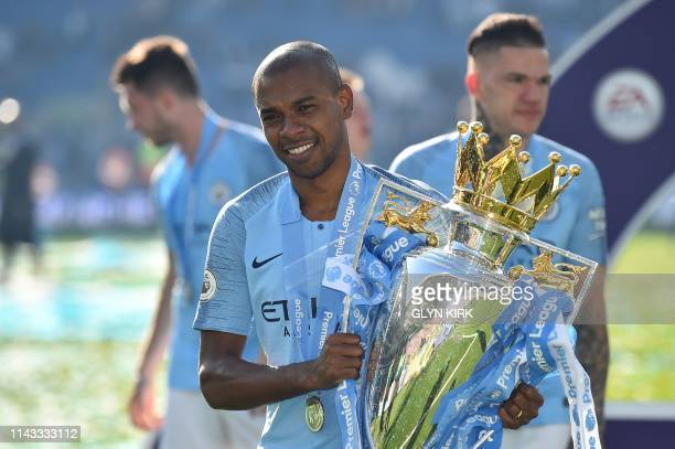 Manchester City's Brazilian midfielder Fernandinho poses with the Premier League trophy after their 4-1 victory in the English Premier League...