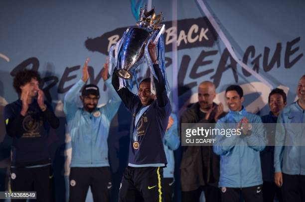 Manchester City's Brazilian midfielder Fernandinho shows the Premier League trophy to supporters outside the Etihad Stadium in Manchester northern...