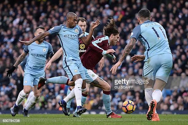 Manchester City's Brazilian midfielder Fernandinho tackles Burnley's Irish midfielder Jeff Hendrick to concede a freekick during the English Premier...