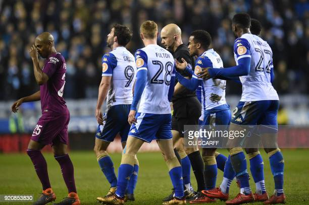 Manchester City's Brazilian midfielder Fernandinho walks as Referee Anthony Taylor walks with Wigan Athletic players after giving a red card to...