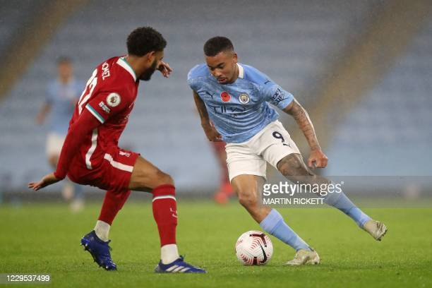 Manchester City's Brazilian striker Gabriel Jesus runs with the ball as Liverpool's English defender Joe Gomez closes in during the English Premier...