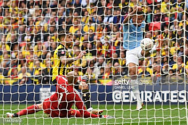 Manchester City's Brazilian striker Gabriel Jesus scores the team's second goal past Watford's Brazilian goalkeeper Heurelho Gomes during the English...
