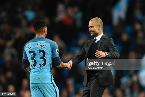 Manchester City's Brazilian striker Gabriel Jesus shakes hands with Manchester City's Spanish manager Pep Guardiola during the English Premier League...
