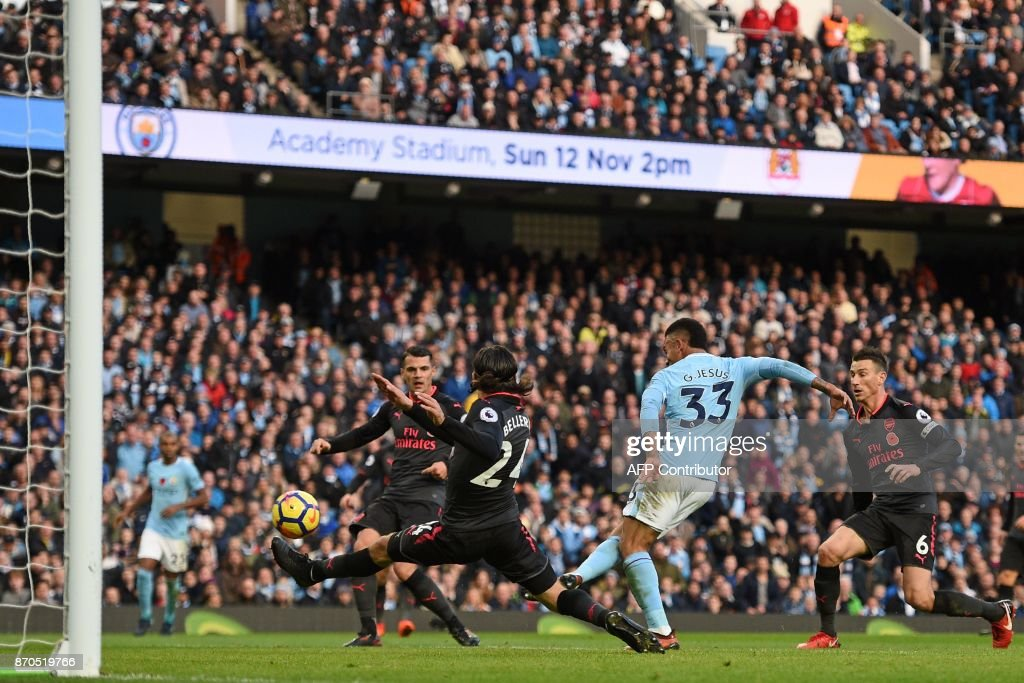 Manchester City's Brazilian striker Gabriel Jesus (2nd R) shoots to score their third goal during the English Premier League football match between Manchester City and Arsenal at the Etihad Stadium in Manchester, north west England, on November 5, 2017. / AFP PHOTO / Oli SCARFF / RESTRICTED TO EDITORIAL USE. No use with unauthorized audio, video, data, fixture lists, club/league logos or 'live' services. Online in-match use limited to 75 images, no video emulation. No use in betting, games or single club/league/player publications. /