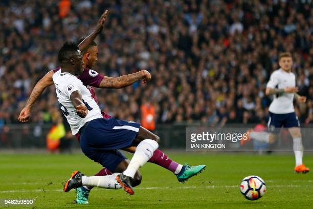 Manchester City's Brazilian striker Gabriel Jesus shoots to score the opening goal under pressure from Tottenham Hotspur's Colombian defender...