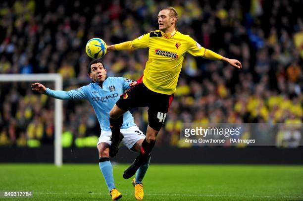 Manchester City's Carlos Tevez and Watford's Joel Ekstrand battle for the ball in the air