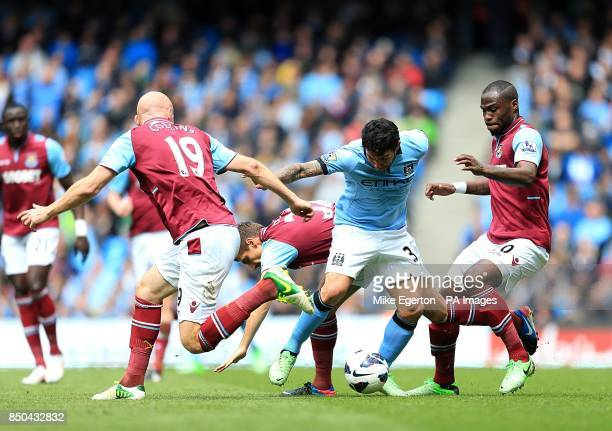 Manchester City's Carlos Tevez battles for the ball with West Ham United's James Collins Gary O'Neil and Guy Demel during the Barclays Premier League...
