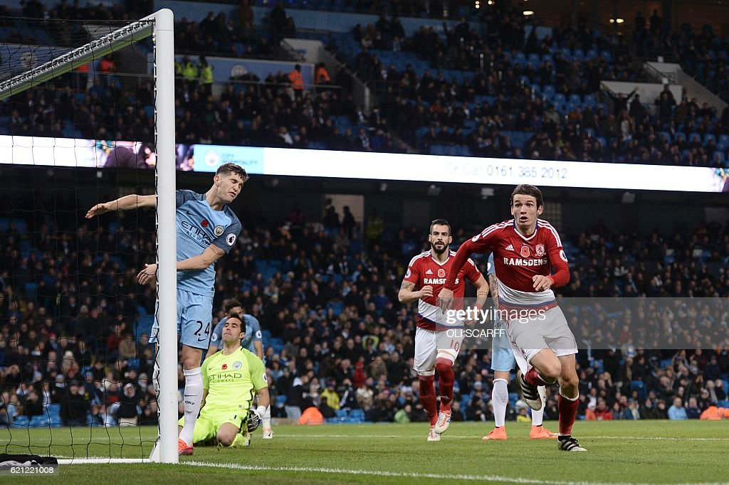 Manchester City's Chilean goalkeeper Claudio Bravo (2L) and Manchester City's English defender John Stones (L) react as Middlesbrough's Dutch midfielder Marten de Roon (R) celebrates scoring a late equalising goal for 1-1 during the English Premier League football match between Manchester City and Middlesbrough at the Etihad Stadium in Manchester, north west England, on November 5, 2016. / AFP / OLI SCARFF / RESTRICTED TO EDITORIAL USE. No use with unauthorized audio, video, data, fixture lists, club/league logos or 'live' services. Online in-match use limited to 75 images, no video emulation. No use in betting, games or single club/league/player publications. /