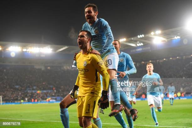 Manchester City's Chilean goalkeeper Claudio Bravo celebrates with Manchester City's Portuguese midfielder Bernardo Silva and other teammates after...
