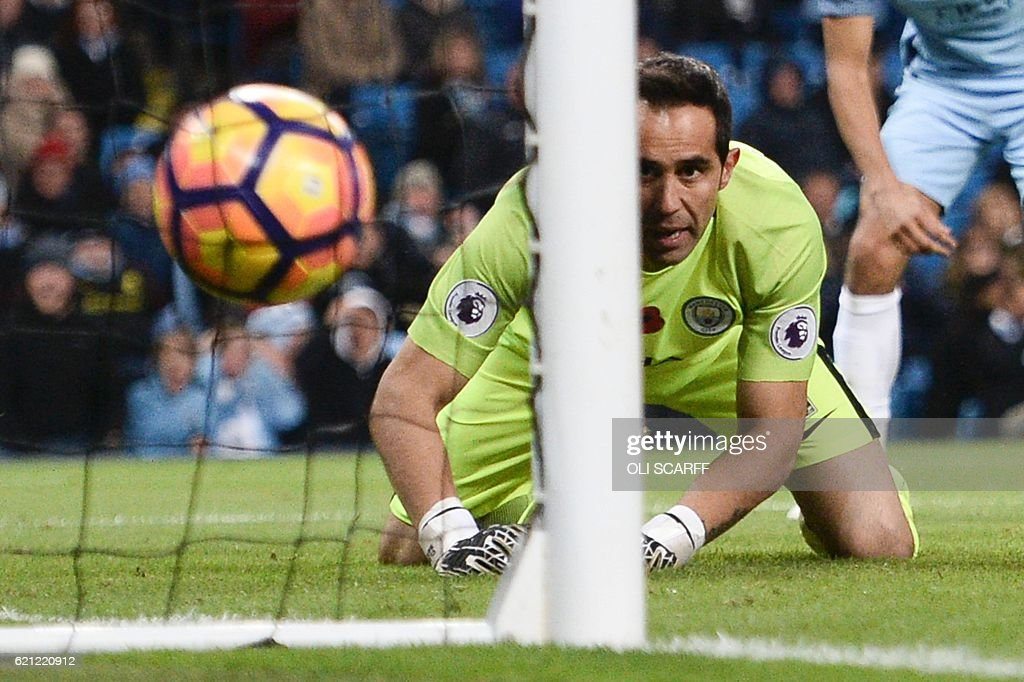 Manchester City's Chilean goalkeeper Claudio Bravo looks at the ball in his net after Middlesbrough's Dutch midfielder Marten de Roon (unseen) scored a late equalising goal for 1-1 during the English Premier League football match between Manchester City and Middlesbrough at the Etihad Stadium in Manchester, north west England, on November 5, 2016. / AFP / OLI SCARFF / RESTRICTED TO EDITORIAL USE. No use with unauthorized audio, video, data, fixture lists, club/league logos or 'live' services. Online in-match use limited to 75 images, no video emulation. No use in betting, games or single club/league/player publications. /
