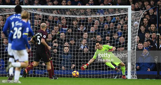 Manchester City's Chilean goalkeeper Claudio Bravo puts out a hand but cannot stop Everton's Belgian striker Kevin Mirallas's shot beating him for...