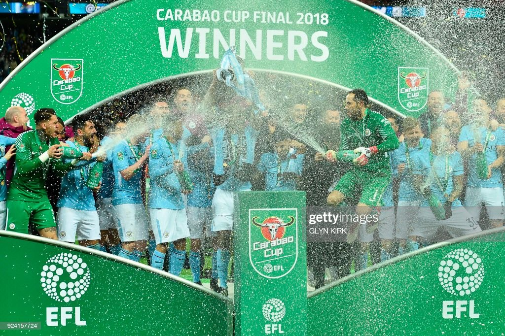 Manchester City's Chilean goalkeeper Claudio Bravo sprays the champagne as City players celebrate with the trophy on the pitch after their victory in the English League Cup final football match between Manchester City and Arsenal at Wembley stadium in north London on February 25, 2018. Manchester City won the first trophy of the Guardiola era on Sunday, thumping a disappointing Arsenal 3-0 in the League Cup final at Wembley. / AFP PHOTO / Glyn KIRK / RESTRICTED TO EDITORIAL USE. No use with unauthorized audio, video, data, fixture lists, club/league logos or 'live' services. Online in-match use limited to 75 images, no video emulation. No use in betting, games or single club/league/player publications. /