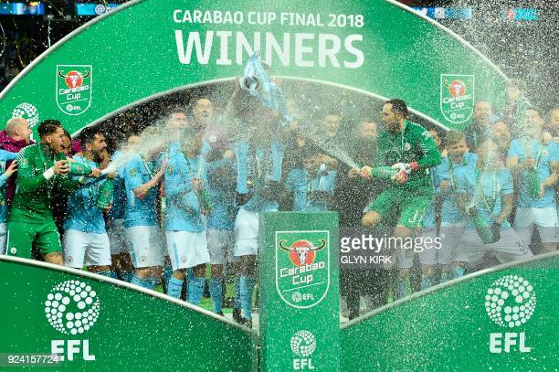 Manchester City's Chilean goalkeeper Claudio Bravo sprays the champagne as City players celebrate with the trophy on the pitch after their victory in...
