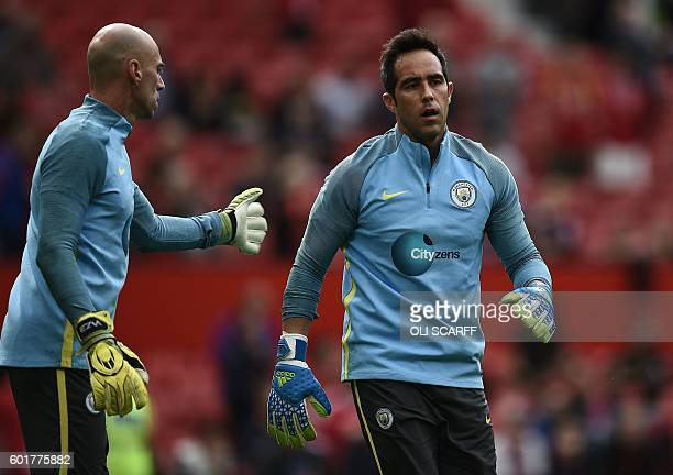 Manchester City's Chilean goalkeeper Claudio Bravo warms up with Manchester City's Argentinian goalkeeper Willy Caballero ahead of the English...