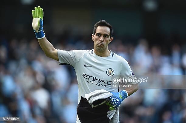 Manchester City's Chilean goalkeeper Claudio Bravo waves as he leaves the pitch at halftime during the English Premier League football match between...