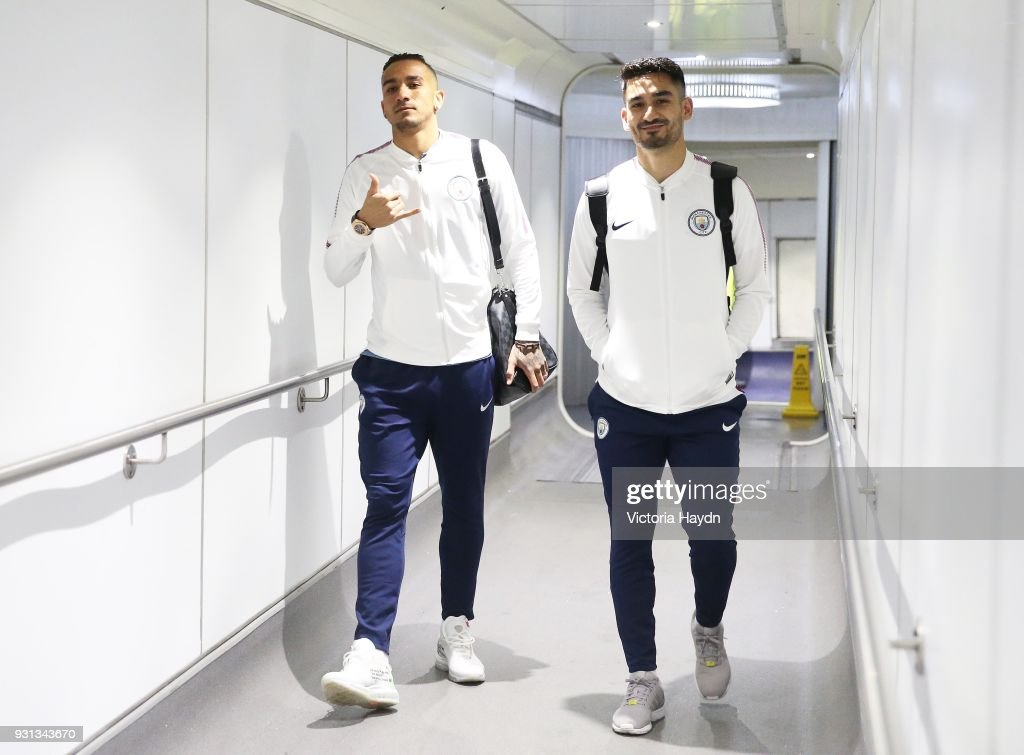 Manchester City's Danilo and Ilkay Gundogan board the flight at Manchester Airport on March 13, 2018 in Manchester, England.